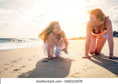 Happy mother and daughter having fun on the beach in vacation - Mom playing with her kid during their holidays - Family lifestyle and love concept