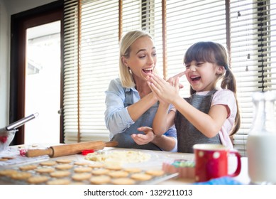 Happy Mother and daughter having fun during preparing the dough, bake cookies in the kitchen.