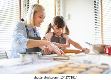 Happy Mother and daughter having fun during kneading dough on kitchen table together. Baking bread.