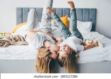 Happy mother and daughter having fun and playing together on the bed at home.