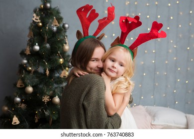 happy mother and daughter hugging and celebrating Christmas at home. Christmas time.  Happy Christmas holidays!