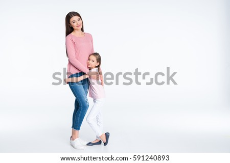 Happy mother and daughter hugging and smiling at camera isolated on white