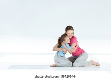 Happy mother and daughter hugging while sitting on yoga mat isolated on white