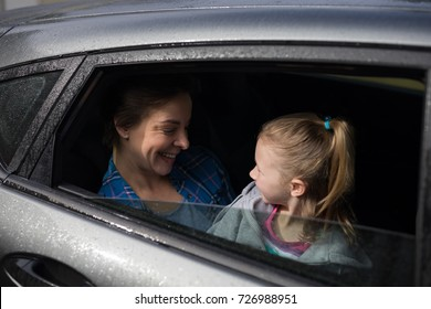 Happy mother and daughter interacting in the back of the car
