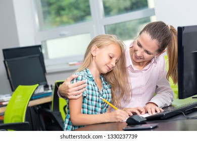 Happy mother and daughter are learning lessons in her mother's office at work. Woman teacher with girl study together sitting at the table near the computer monitor.