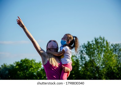 Happy mother and daughter. Little daughter is talking to her mother. Masked mother and little daughter walk during quarantine due to coronavirus pandemic