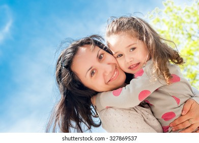 Happy mother and daughter look in the camera and laugh. The picture is photographed from below, the bright blue sky as a background.