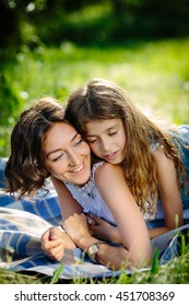 Happy mother and daughter lying outdoors smiling and hugging