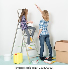 Happy mother and daughter makes repairs at home.