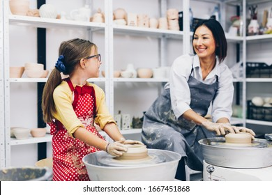 Happy mother and daughter making clay pottery on a spin wheel.
