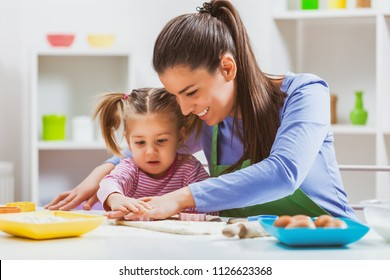 Happy mother and daughter are making cookies in their kitchen.