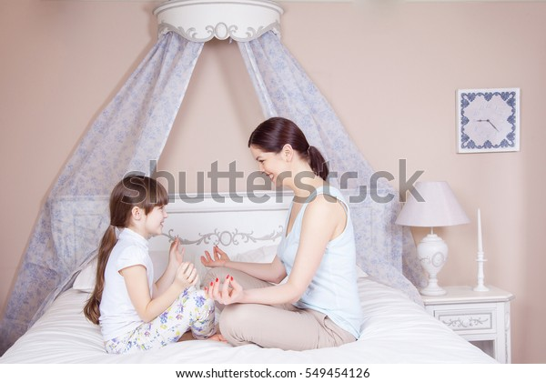 Happy mother and daughter meditating and smiling while sitting in yoga pose on the bed at home. Studio shot.