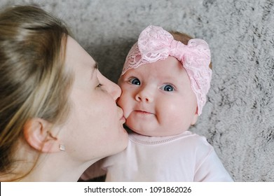 Happy mother and daughter. Mom kisses little baby girl, concept happy family, lifestyle. newborn lies on the bed. Photo shoot 4-5 months. flat lay. top view.