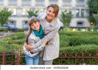 Happy mother and daughter on a background of a city park.