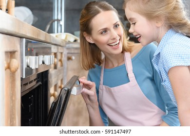 Happy mother and daughter opening oven while baking cookies