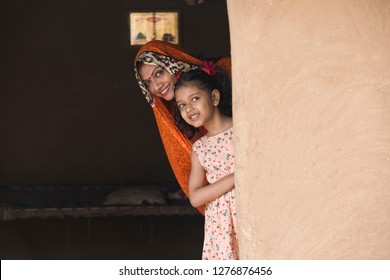Happy mother and daughter peeking from rural house