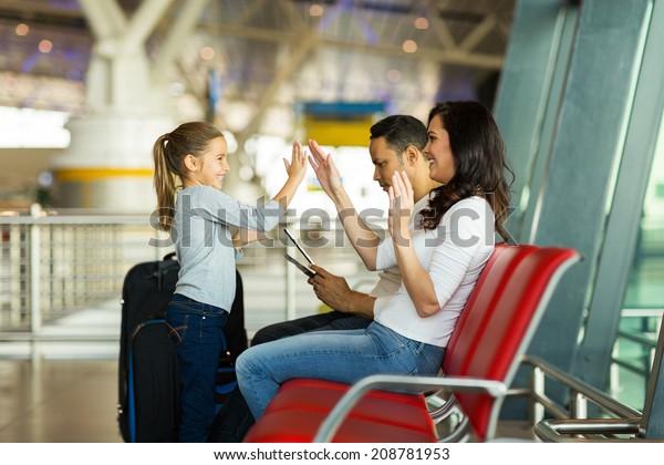搭乗前に空港でゲームをする幸せな母と娘