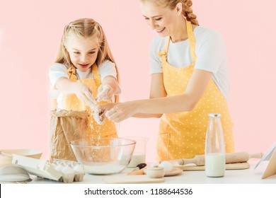 happy mother and daughter pouring flour into bowl while cooking together isolated on pink