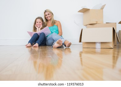 Happy mother and daughter reading a book together on the floor near moving boxes