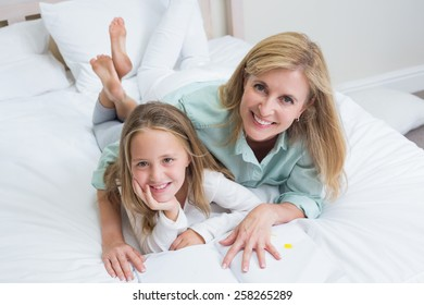 Happy mother and daughter reading a book in bed