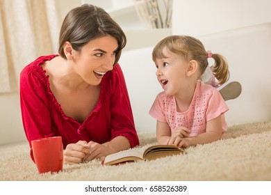 Happy mother and daughter reading book on carpet