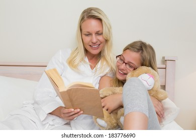 Happy mother and daughter reading novel together in bed at home