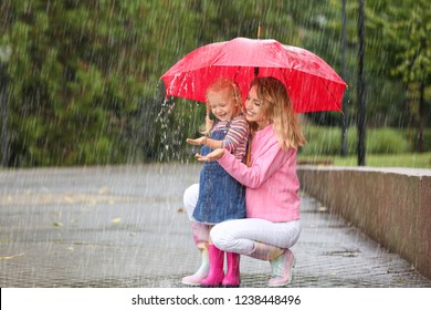 Happy mother and daughter with red umbrella in park on rainy day. Space for text