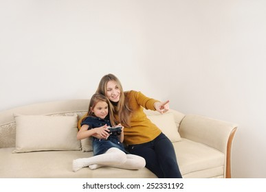 happy mother and daughter relaxing and playing TV games on the sofa at home, happy family concept