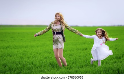 Happy mother and daughter run on the meadow