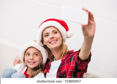 happy mother and daughter in santa hats taking selfie with smartphone