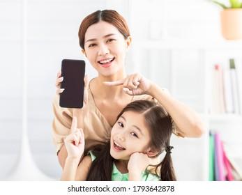 glückliche Mutter und Tochter, die ihr Handy zeigen