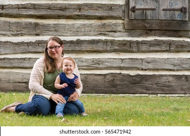 Happy mother and daughter sitting in the grass in front of an old house