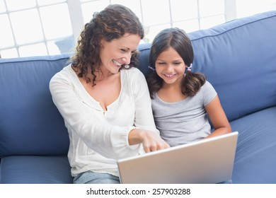 Happy mother and daughter sitting on the couch and using laptop in the living room
