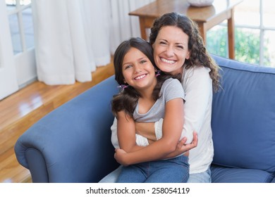 Happy mother and daughter sitting on the couch and smiling at camera in the living room