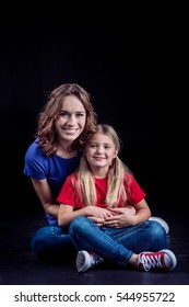 Happy mother and daughter sitting together and smiling at camera isolated on black