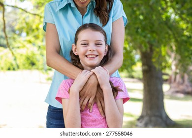 Happy mother and daughter smiling at the camera on a sunny day