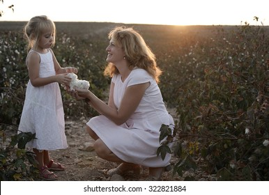 happy mother with daughter standing on a cotton field in sunset colors