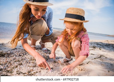 happy mother and daughter in straw hats collecting seashells at beach