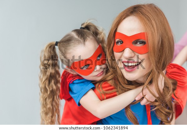 happy mother and daughter in superhero costumes having fun together isolated on grey