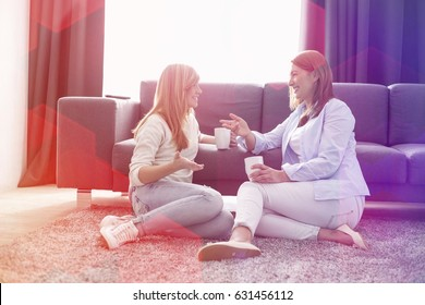 Happy mother and daughter talking while having coffee in living room