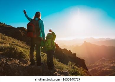 feliz madre e hija viajan en las montañas al atardecer