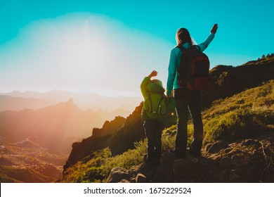 happy mother and daughter travel in sunset mountains