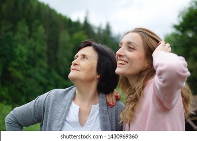 Happy mother and daughter traveling and posing together over landscape of forest and mountains