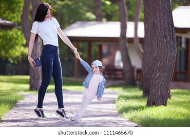 Happy mother and daughter walking in the park. Beauty nature scene with family outdoor lifestyle at spring or summer time. Happy stilish family resting together, having fun outdoor.