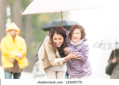 Happy mother and daughter walking in park. Smiling parent and kid hiding under umbrella. Laughing woman and child outdoors. People with umbrellas and person in yellow raincoat in background.