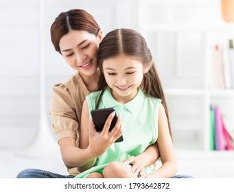 glückliche Mutter und Tochter, die das Smartphone guckt