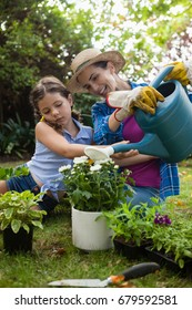 Happy mother with daughter watering potted plants while sitting on field in backyard