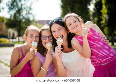 Happy mother with daughters eating ice cream. Togetherness and bonding.