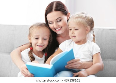 Happy mother with daughters reading book