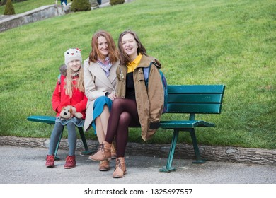 happy mother and daughters  sitting on a bench smiling and looking at the camera, France